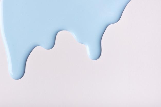 Hellblaue flüssigkeitstropfen der farbfarbe fließen auf weißem hintergrund nach unten. abstrakter himmelhintergrund mit fließendem tropfmuster.