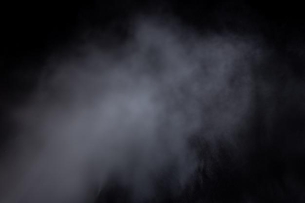 Hellblaue rauchwolken auf schwarzem hintergrund isoliert. gas explodiert, wirbelt im weltraum. abstraktion, klassisches blau, trendfarbe, farbe 2020