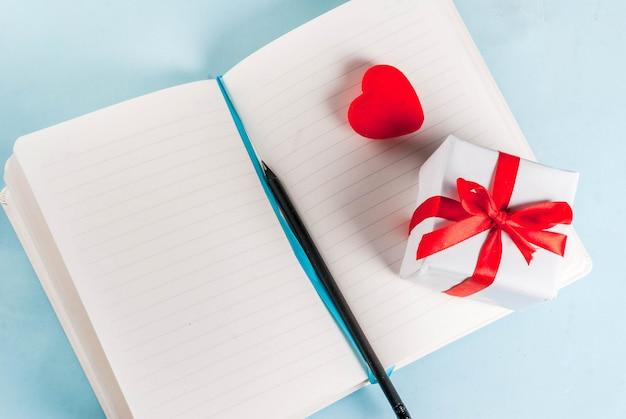 Hellblauer hintergrund des valentinstags. rotes herz, geschenk, notizblock und bleistift