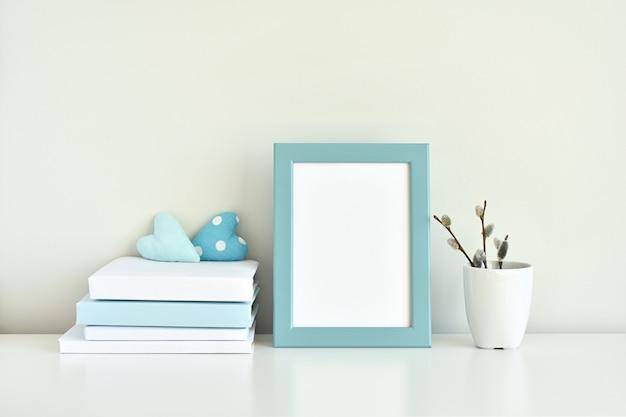 Hellblauer innenraum, leeres fotorahmenmodell, bücher, weiße und blaue dekorationen.