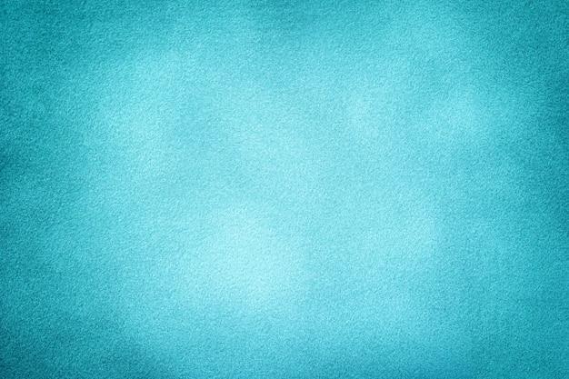 Hellblauer matter hintergrund des wildlederstoffes mit vignette, nahaufnahme. samt textur von cyan gefälschten textil mit farbverlauf, makro.