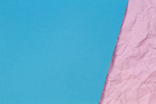 Hellblaues leeres papierblatt über pastellrosa zerknittertem faltigem papierbeschaffenheitshintergrund