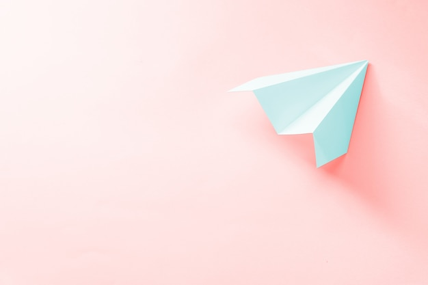 Hellblaues papierflugzeug auf koralle