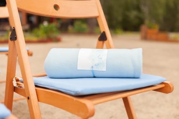 Hellblaues plaid auf einem braunen stuhl, das konzept einer warmen hochzeit, nahaufnahme