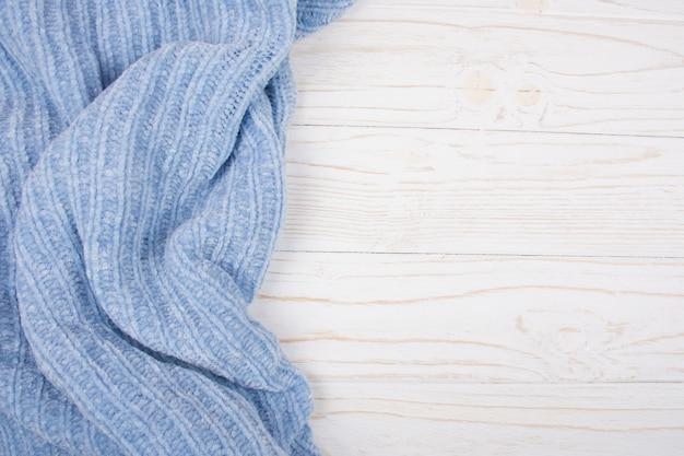 Hellblaues wollgewebe auf einem weißen hölzernen hintergrund
