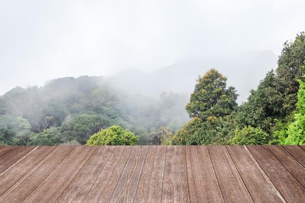 Hellbraune farbe des holztischs mit berg und nebel ein hintergrund.