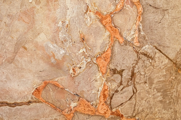 Hellbraune wand mit orangefarbenem steinoberflächenbeschaffenheitshintergrund