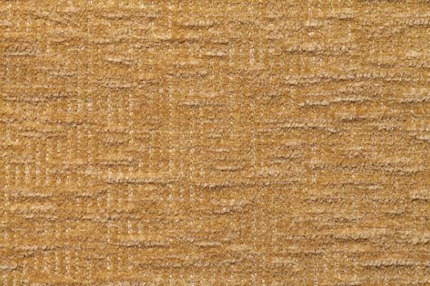 Hellbrauner flauschiger hintergrund aus weichem, flauschigem stoff. beschaffenheit der textilnahaufnahme.