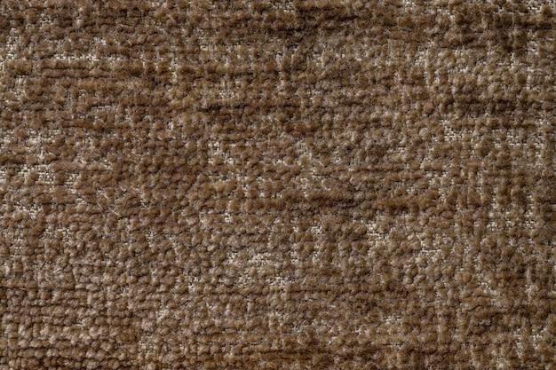 Hellbrauner flauschiger hintergrund aus weichem, flauschigem stoff. beschaffenheit der textilnahaufnahme