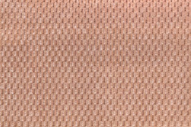 Hellbrauner hintergrund von weicher flauschiger stoffnahaufnahme. textur des textilmakros