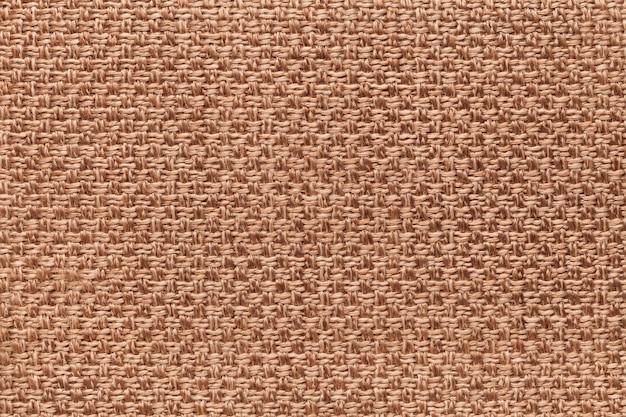 Hellbrauner textilhintergrund mit kariertem design, nahaufnahme. struktur des gewebemakros.