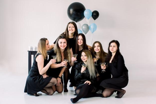 Helle ausdrucksformen der glücklichen gefühle von sieben erstaunlichen mädchen, die partei auf weißem hintergrund feiern. schwarze luxuskleider, lächelnd, große luftballons, stilvoller look. geburtstagsfeier-konzept