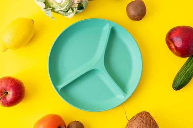 Helle babytadellose platte mit teilern auf gelber oberfläche. leere teller für lebensmittel