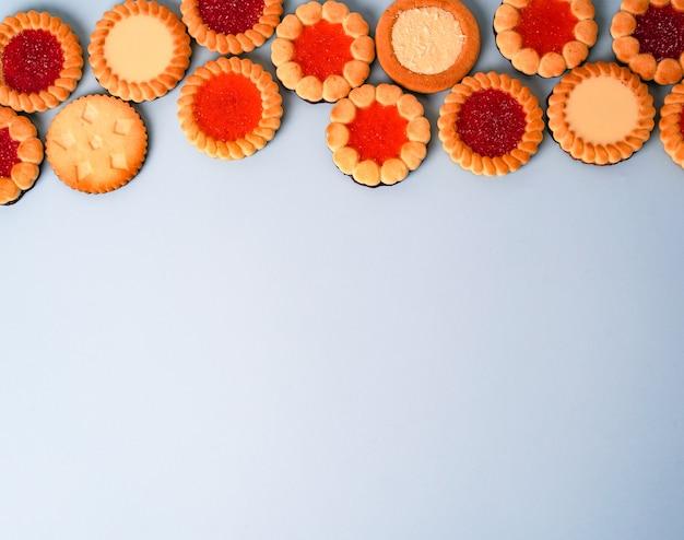 Helle biscotti-kekse mit verschiedenen füllungen auf hellgrau-blauem hintergrund. foto in hoher qualität