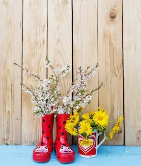 Helle blumen in töpfen, rote gummistiefel auf einem hölzernen hintergrund. frühlingsblumenstillleben. valentinstag