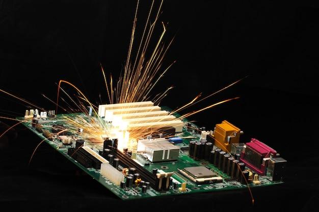 Helle brennende funken fliegen vom chip komplexer elektronischer geräte auf dunklem hintergrund