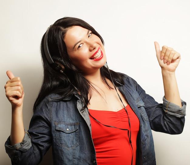 Helle brunettefrau mit hörender musik der kopfhörer