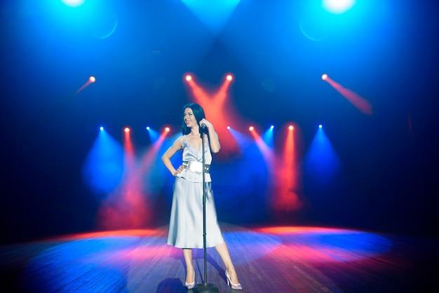 Helle bühnenbeleuchtung. sänger singt zum mikrofon.