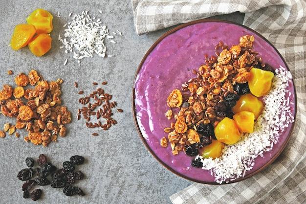 Helle bunte acai-schale mit müsli und getrockneten früchten.
