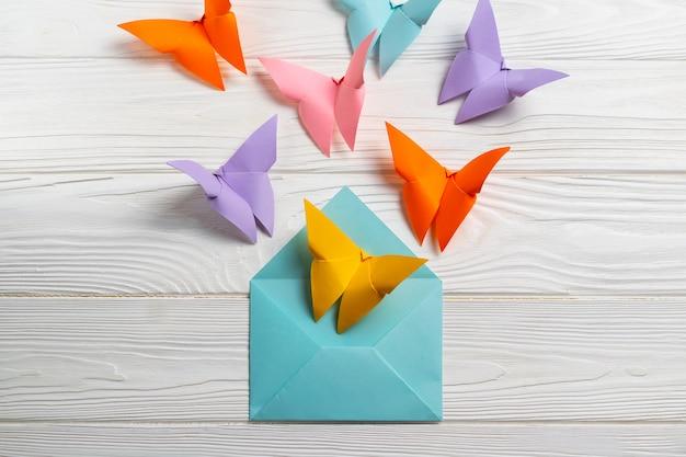 Helle bunte butterfeilen aus papier fliegen aus dem umschlag.