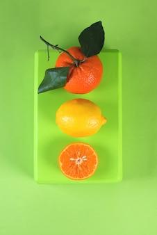 Helle bunte flache lage von mandarinen, zitronen und tropischen blättern