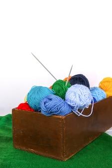 Helle bunte knäuel aus garn und stricknadeln in einer holzkiste auf weißem hintergrund mit grüner strickmatte.