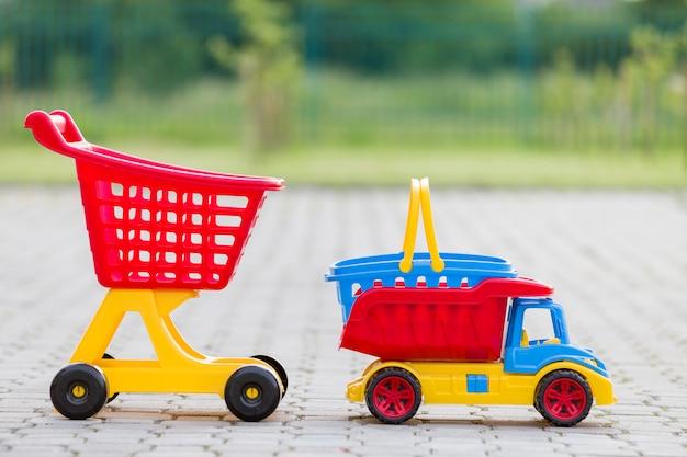 Helle bunte plastikspielwaren für kinder draußen am sonnigen sommertag. auto lkw, einkaufskorb und handwagen.