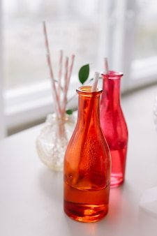 Helle cocktailflaschen mit tuben erfrischende limonade