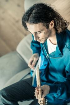 Helle elektronische gitarre. durchdachter gutaussehender gitarrist, der sein musikinstrument spielt, während er sich auf einer grauen couch ausruht