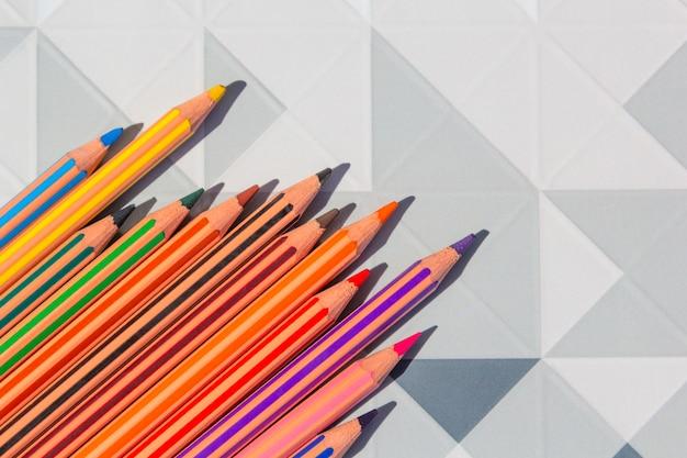 Helle farbbleistifte auf modernem niedrigem poly, geometrisches abstraktes design des polygons.
