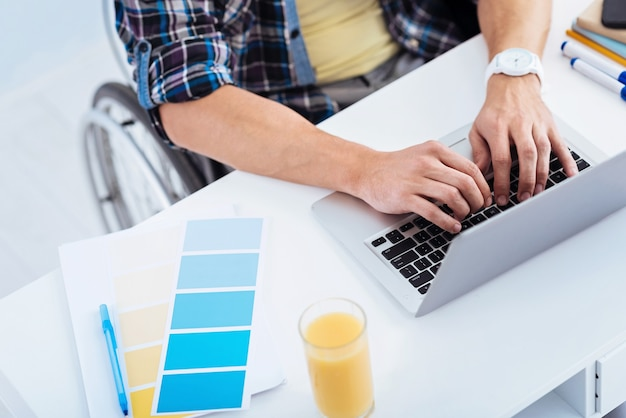 Helle farben. kompetenter arbeiter, der computer benutzt, während er artikel tippt und in seinem rollstuhl sitzt