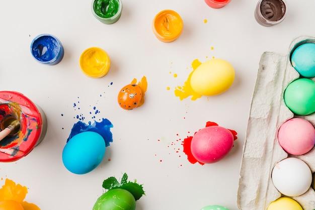 Helle farbige eier in der nähe von behälter, pinsel und wasserfarben