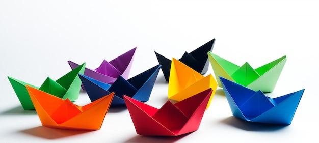 Helle farbige papierboote auf einem weißen hintergrund. speicherplatz kopieren
