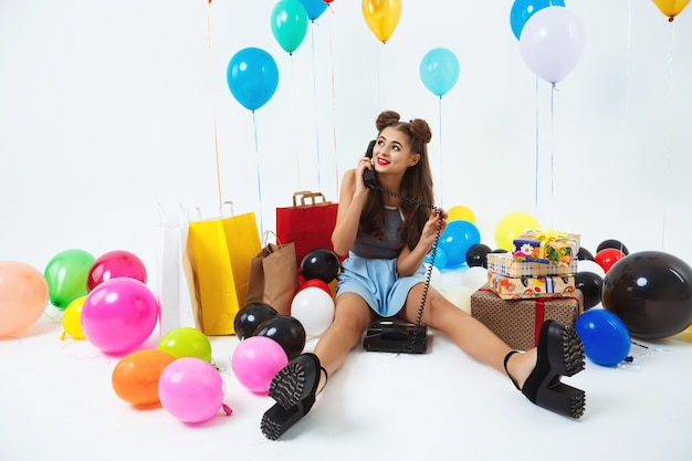 Helle geburtstagsfeier. netter mode mädchen telefonhörer in händen
