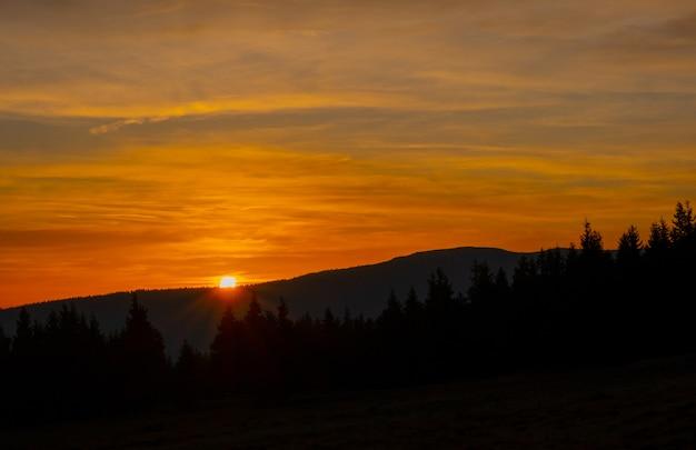 Helle gelbe orange des sonnenunterganggebirgshimmelblaus der bunten herbstsonne bewölkt baumrauch-nebeldunst
