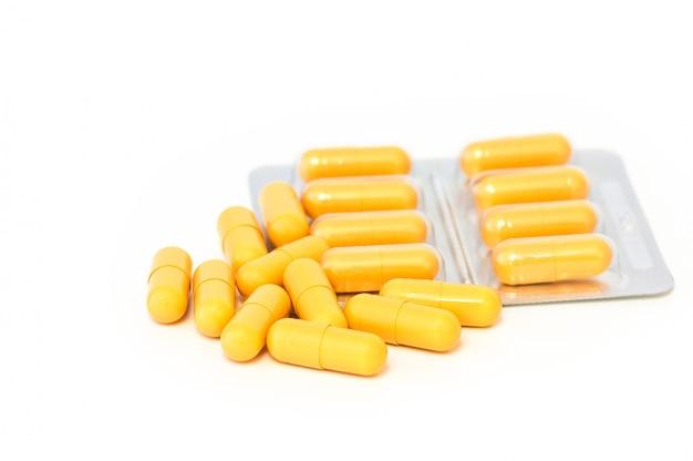 Helle gelbe pillen und blasen zerstreuten auf einen weißen hintergrund.