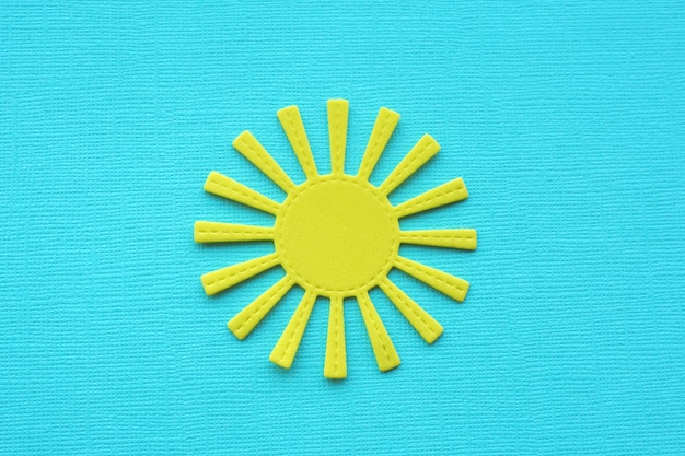Helle gelbe sonne auf blauem strukturiertem papier.