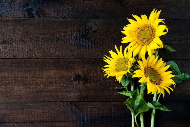 Helle gelbe sonnenblumen auf natürlichem rustikalem hölzernem brett