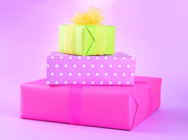Helle geschenke mit bögen auf lila hintergrund
