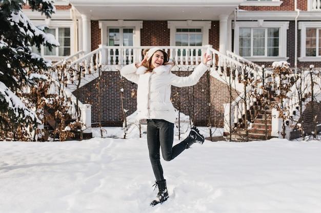 Helle glückliche wahre gefühle der lustigen frau, die sonniges winterwetter auf straße genießt. freudige hübsche junge frau in der warmen kleidung, die spaß gefroren im freien hat.