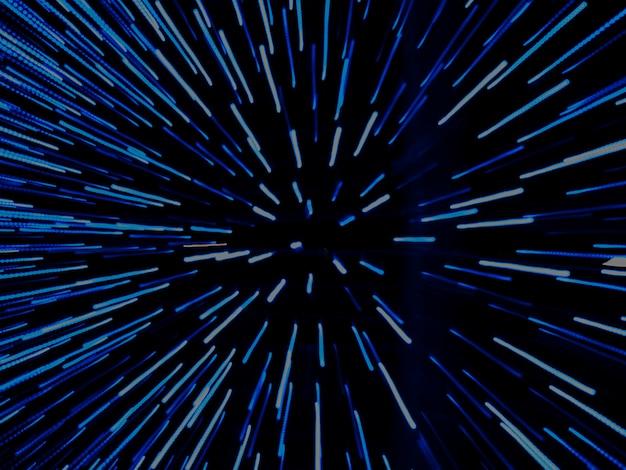 Helle hellblaue lichter schießen aus der mitte heraus, zoom-effekt in unschärfe. dunkelblauer hintergrund