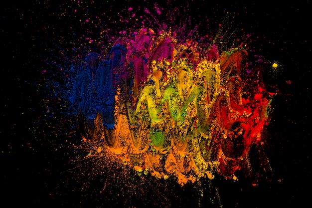 Helle holi farben gemischt mit dem finger über schwarzem hintergrund