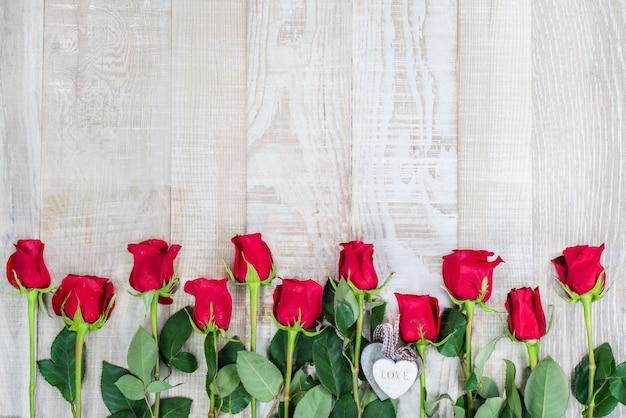 Helle holzoberfläche mit rahmen aus rosen und holzherzen
