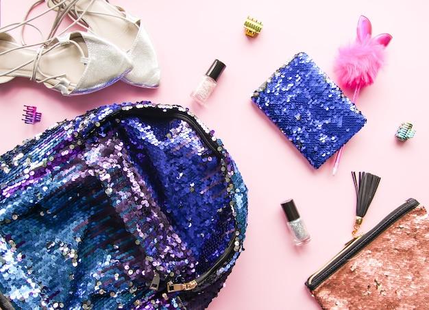 Helle komposition von modeaccessoires. glitzerpailletten-kosmetiktasche, bunter rucksack, nagellacke, notizblock und schuhe objekt auf weichem pastellhintergrund. flache lage, ansicht von oben.