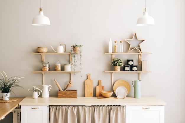 Helle küche im provence-stil mit zimmerpflanzen aus holz und accessoires auf dem tisch