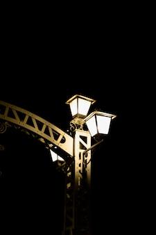 Helle lampe am gatter gegen dunklen hintergrund