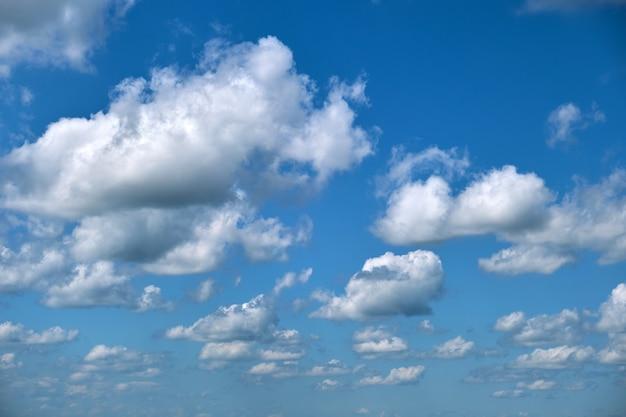 Helle landschaft aus weißen geschwollenen kumuluswolken am blauen klaren himmel.
