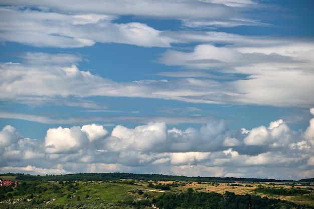 Helle landschaft von weißen geschwollenen kumuluswolken am blauen klaren himmel über ländlichem gebiet.