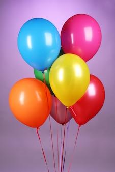 Helle luftballons auf lila hintergrund