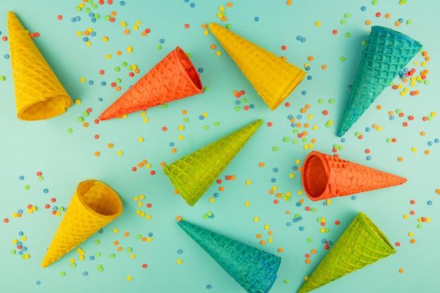 Helle mehrfarbige eiswaffeltüten auf blauer oberfläche mit verstreuten konfetti-zuckerstreuseln.